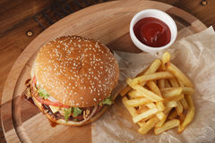 Cheeseburger burger με τις τηγανιτές πατάτες και τη σάλτσα Στοκ Εικόνα