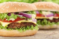 Cheeseburger burger χάμπουργκερ οι στενές επάνω ντομάτες βόειου κρέατος κινηματογραφήσεων σε πρώτο πλάνο αφήνουν Στοκ Εικόνες