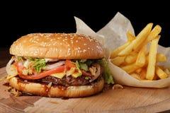 Cheeseburger & x28; burger& x29; com batatas fritas e molho Foto de Stock Royalty Free
