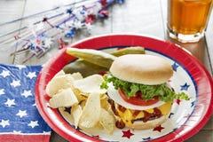 Cheeseburger caricato ad un cookout di tema patriottico Immagini Stock
