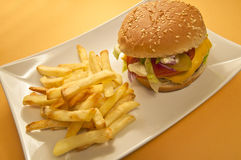 Cheeseburger and chips. On a plate, yellow background Royalty Free Stock Images
