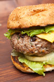 Cheeseburger close-up on wooden table. Large tasty cheeseburger on sesame bun close-up on wooden table Stock Photo