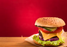 Cheeseburger closeup on red background Royalty Free Stock Photo