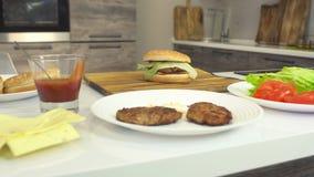 Cheeseburger cocinado jugoso fresco en una cocina moderna y productos, ingredientes para una hamburguesa y cheeseburger almacen de video