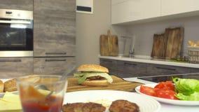 Cheeseburger cocinado jugoso fresco en una cocina moderna y productos, ingredientes para una hamburguesa y cheeseburger almacen de metraje de vídeo