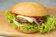 Cheeseburger com alface, tomate, e cebola em um bolo do bolo frito foto de stock