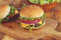 Cheeseburger com cebola e alface do tomate foto de stock