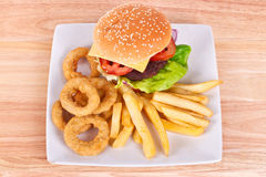Cheeseburger com microplaquetas e anéis de cebola Fotografia de Stock Royalty Free