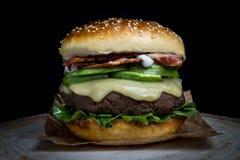 Cheeseburger con bacon, l'avocado, la lattuga e la maionese fotografie stock libere da diritti
