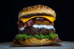 Cheeseburger con bacon, lattuga, cheddar, gli anelli di cipolla e la maionese immagini stock libere da diritti