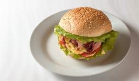 Cheeseburger con il prosciutto, il pomodoro e l'insalata Fotografie Stock Libere da Diritti