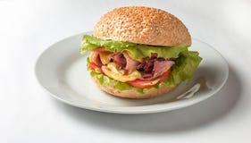 Cheeseburger con il prosciutto, il pomodoro e l'insalata Immagine Stock