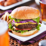 Cheeseburger con la cerveza y las patatas fritas Foto de archivo libre de regalías