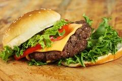 Cheeseburger con la cipolla e la lattuga del pomodoro Immagini Stock