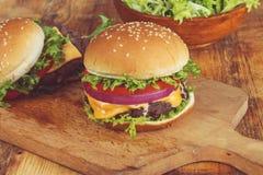 Cheeseburger con la cipolla e la lattuga del pomodoro Fotografia Stock