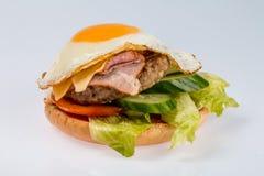 Cheeseburger con la cotoletta del manzo, il bacon, i pomodori e le fette del formaggio, condite con salsa ed insalata verde per u fotografie stock