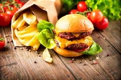 Cheeseburger con la ensalada y las patatas fritas frescas Fotos de archivo libres de regalías
