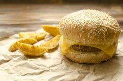Cheeseburger con le patate ed il peperoncino rosso fritti su una carta del mestiere sopra immagini stock libere da diritti