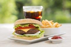 Cheeseburger con le patate fritte e la bevanda fresca Fotografia Stock