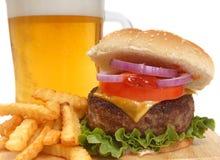 Cheeseburger con le patate fritte e la birra Fotografia Stock