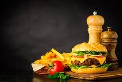 Cheeseburger con le patate fritte e lo spazio della copia Fotografia Stock Libera da Diritti