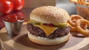 Cheeseburger con los anillos y las fritadas de cebolla almacen de metraje de vídeo