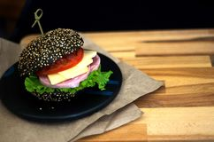 Cheeseburger con tocino y un bollo negro que miente en un tablero de madera foto de archivo
