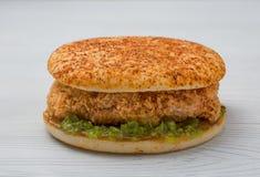 Cheeseburger con un pepino del pollo y de la salmuera en un fondo blanco Fotografía de archivo libre de regalías