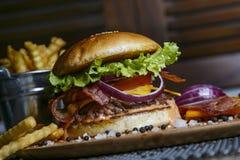 Cheeseburger d'été avec la tomate et l'oignon Photographie stock libre de droits