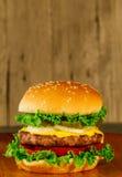 Cheeseburger de lujo clásico con lechuga, las cebollas, el tomate y las salmueras Imágenes de archivo libres de regalías