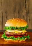 Cheeseburger de lujo clásico con lechuga, las cebollas, el tomate y las salmueras Fotografía de archivo
