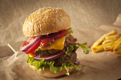 Cheeseburger de lujo clásico con lechuga, las cebollas, el tomate y las salmueras en un bollo de la semilla de sésamo Imagen de archivo