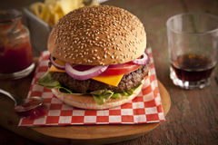 Cheeseburger de lujo clásico con lechuga, las cebollas, el tomate y las salmueras en un bollo de la semilla de sésamo Fotos de archivo