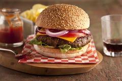 Cheeseburger de lujo clásico con lechuga, las cebollas, el tomate y las salmueras en un bollo de la semilla de sésamo Foto de archivo