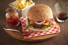 Cheeseburger de lujo clásico con lechuga, las cebollas, el tomate y las salmueras en un bollo de la semilla de sésamo Fotos de archivo libres de regalías