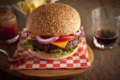 Cheeseburger de luxe classique avec de la laitue, les oignons, la tomate et les conserves au vinaigre sur un petit pain de la gra Photos stock