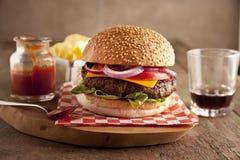Cheeseburger de luxe classique avec de la laitue, les oignons, la tomate et les conserves au vinaigre sur un petit pain de la gra Images stock