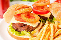 Cheeseburger. And deep fried onion rings.Selective focus on the meat Royalty Free Stock Photos