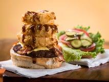 Cheeseburger del bacon con la pila di anelli di cipolla fotografie stock libere da diritti