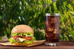 Cheeseburger delicioso com ingredientes da salada em um rissol de carne grelhado em uma tabela de madeira rústica com copyspace Imagens de Stock Royalty Free