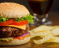 Cheeseburger Deluxe with Potato Chips. A deluxe cheeseburger with tomatoes, onions, pickles, and lettuce with potato chips and cola Royalty Free Stock Image