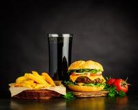 Cheeseburger di sguardo saporito con cola e le patate fritte Fotografia Stock Libera da Diritti