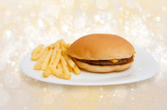 Cheeseburger on dinner plate with french fries Royalty Free Stock Images