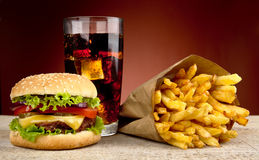 Cheeseburger with drink of cola and french fries on red spotlight stock photos