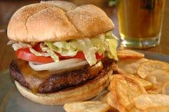 Cheeseburger e una birra Immagini Stock Libere da Diritti
