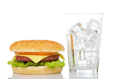 Cheeseburger and empty glass Royalty Free Stock Photography