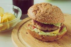 Cheeseburger en la placa de madera Fotografía de archivo