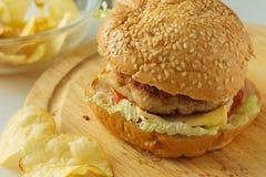 Cheeseburger en la placa de madera Foto de archivo libre de regalías