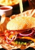 Cheeseburger fait maison savoureux sur un petit pain de sésame Photographie stock libre de droits