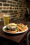 Cheeseburger French Fries and Beer. Photograph of a hamburger french fries and a cold beer on a wood table with a brick background royalty free stock image